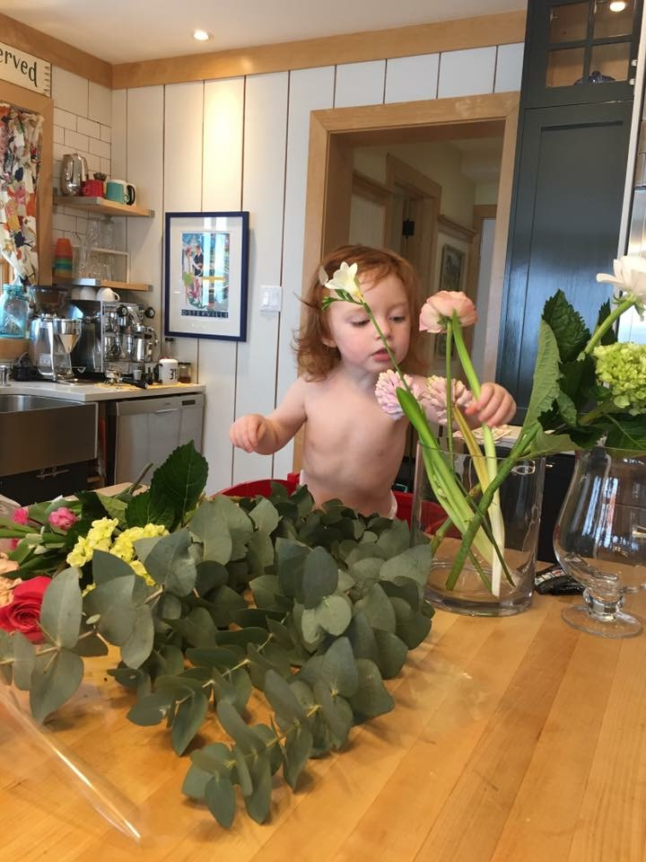 child putting flowers in vase