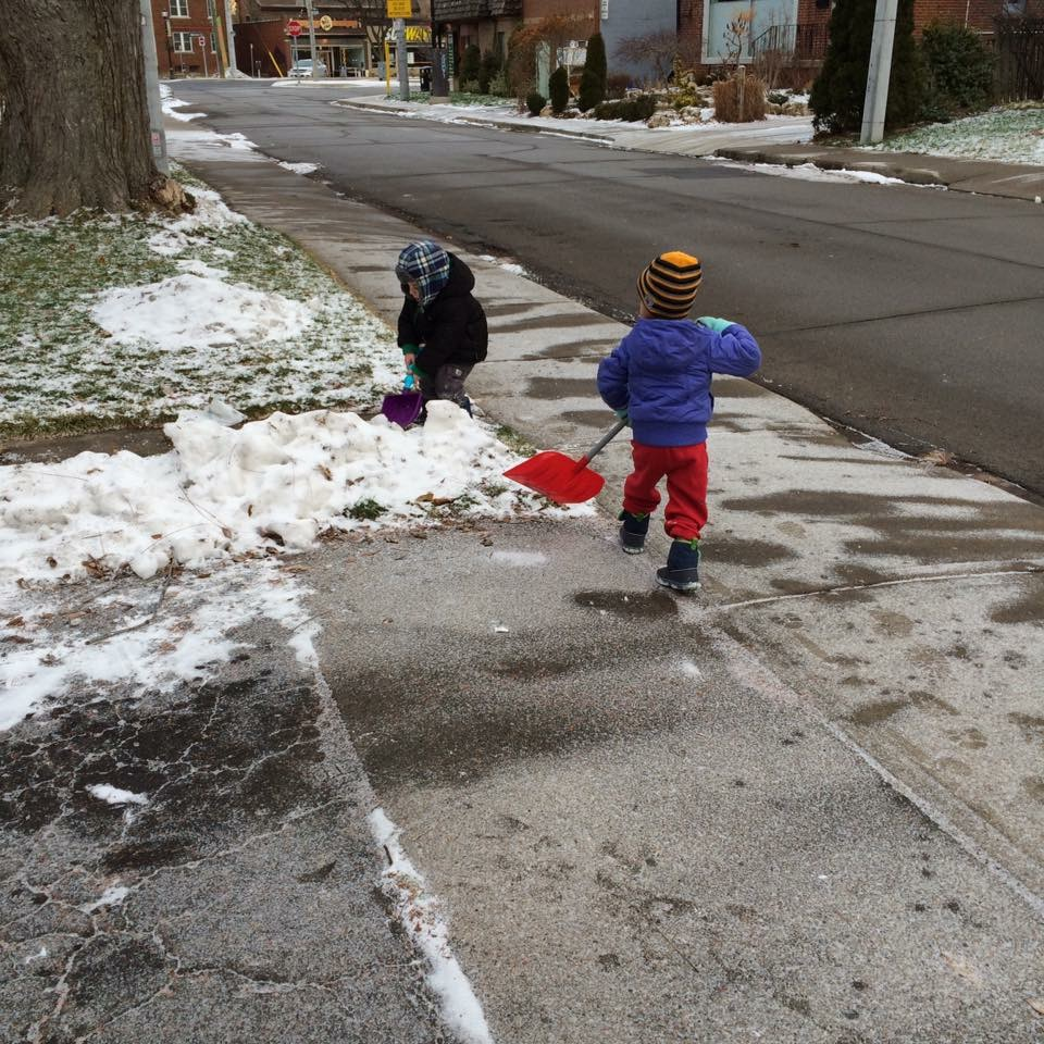 toddler shovelling snow