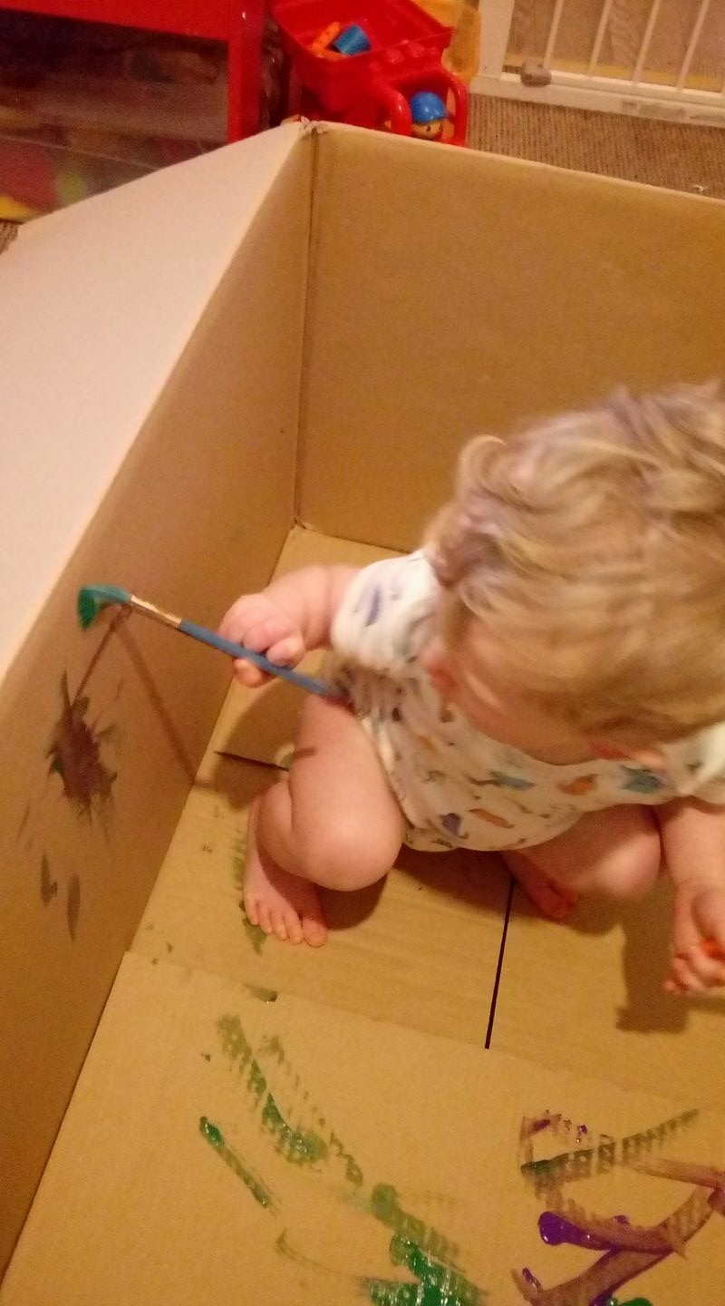 toddler painting inside box