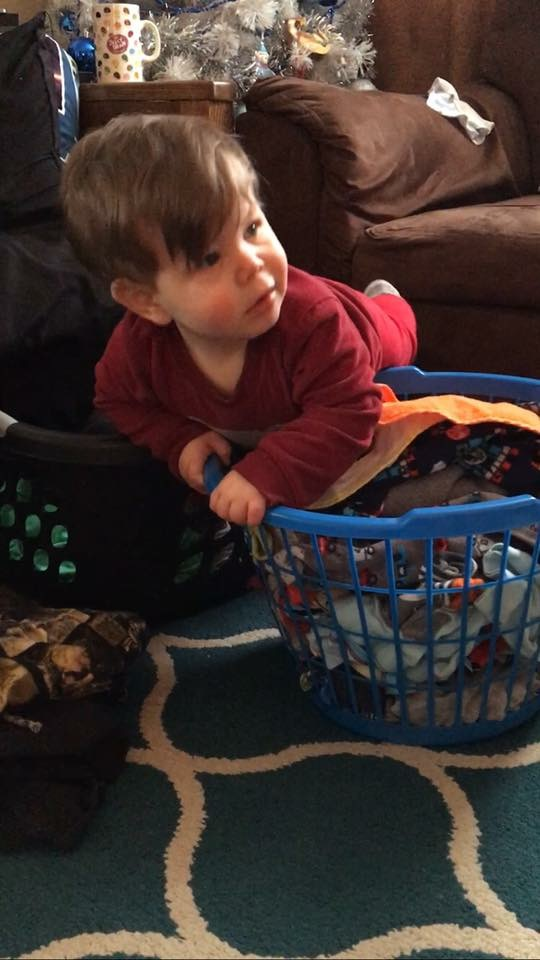 baby climbing in laundry basket